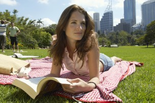 Young woman lying on blanket in park reading book